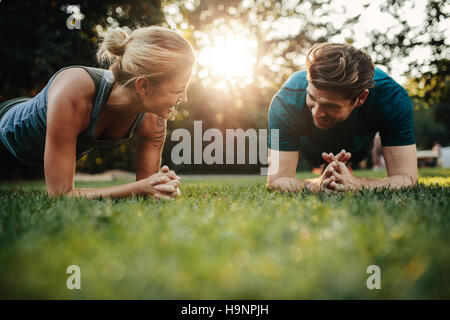 Fit young man and woman exercising in park. Smiling caucasian couple doing core workout on grass. - Stock Photo