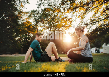 Shot of young couple sitting at park and working out. Man and woman exercising at park in morning. - Stock Photo