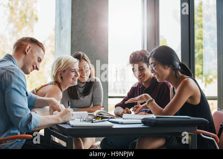 Happy young university students studying with books in library. Group of multiracial people in college library. - Stock Photo