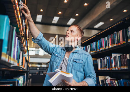 Shot of young male student selecting book from library shelf. University student studying in library. - Stock Photo