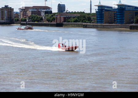 A ferry and speedboat travelling along the River Thames near Canary Wharf pier, London.  14th July 2014. - Stock Photo