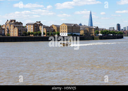 A view of London's skyline, including the Shard building with a speedboat travelling along the River Thames in the - Stock Photo