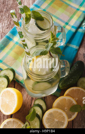 Homemade cucumber lemonade with ice and mint close up in a glass jar on the table. vertical view from above - Stock Photo