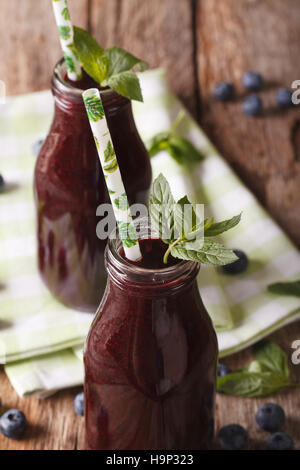 Fresh healthy blueberry juice in a glass bottle on a table macro. vertical - Stock Photo