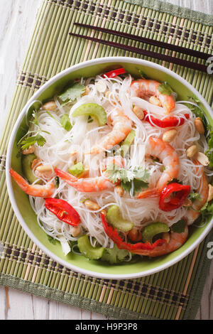 Thai salad with glass noodles, prawns and vegetables macro in a bowl. vertical view from above - Stock Photo