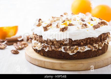 Homemade carrot and walnut cake with zesty orange icing on white wooden table - Stock Photo