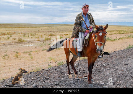 Kazakh man on his horse in the steppes of Kazakhstan. - Stock Photo