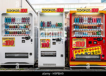 Japan, Osaka, Shinsekai. Three soft drink vending machines, 2 white, 1 red, in row in street. All with signs showing - Stock Photo