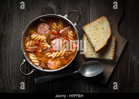 Fresh bean stew with sausage and pasta on wooden background - Stock Photo