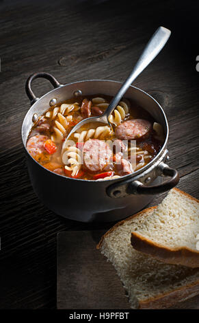 Hot stew with sausage, beans and pasta on wooden background - Stock Photo