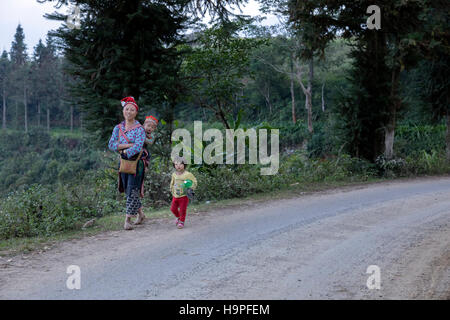 ethnic Red Dao woman with children in the tribal village near Sapa, Vietnam, Asia - Stock Photo