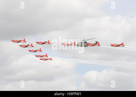 Swiss Air Force PC-7 Team flying in formation  with a Super Puma - Stock Photo
