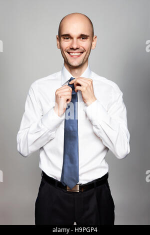 Portrait of smiling man in white shirt fixing his tie. - Stock Photo