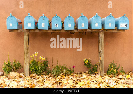 A group of blue mailboxes mounted on a wood stand on the sidewalk, backed by an adobe style wall - Stock Photo