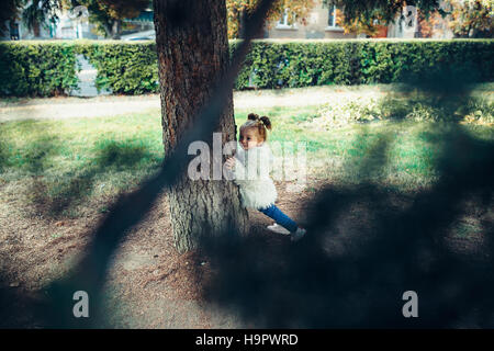 Cute little girl is playing outdoors - Stock Photo