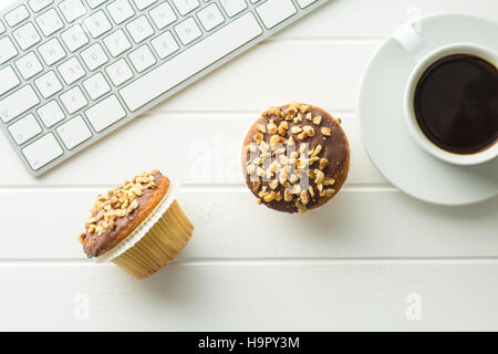 Break for coffee and muffin at the office. Concept with coffee, muffin and computer keyboard. - Stock Photo
