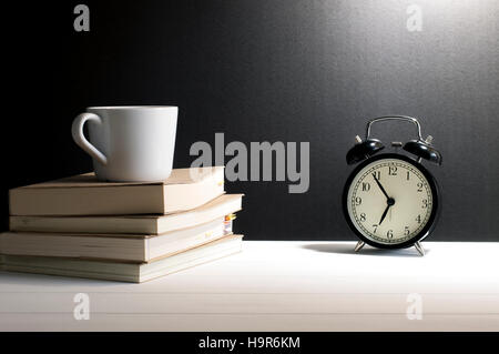 Still life retro alarm clock and a cup of coffee on old books on white wooden table in font of grunge black background. - Stock Photo