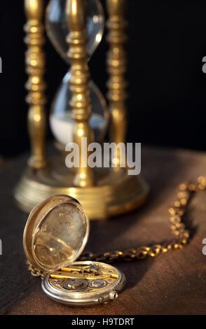 Blurred sandglass on the background of an antique pocket watch - Stock Photo