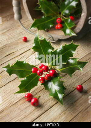 Holly leaves (Ilex), Christmas decoration with red berries on wood - Stock Photo