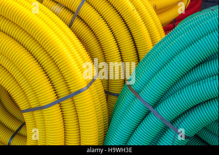 reels of plastic pipes used for land drains reeled up in builders yard. - Stock Photo