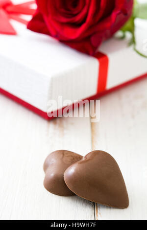 White gift box, roses and chocolate with heart shape on wooden table.copyspace - Stock Photo