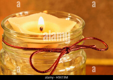 Candle  in a jar with red bow and golden background - Stock Photo