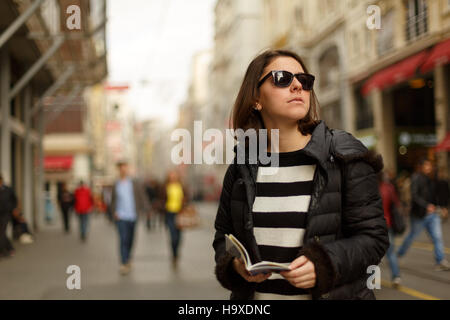 Young woman is on the street and looking for a place to visit ,they are using a travel guide to explore where they - Stock Photo