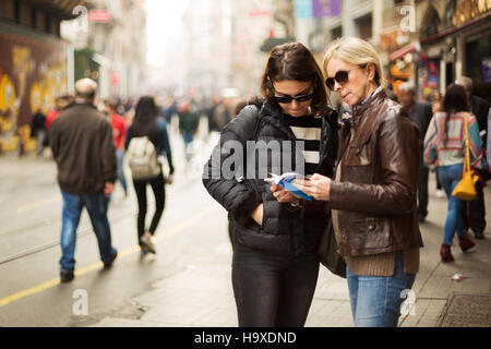 Mother and daughter are on the street and looking for a place to visit ,they are using a travel guide to explore - Stock Photo