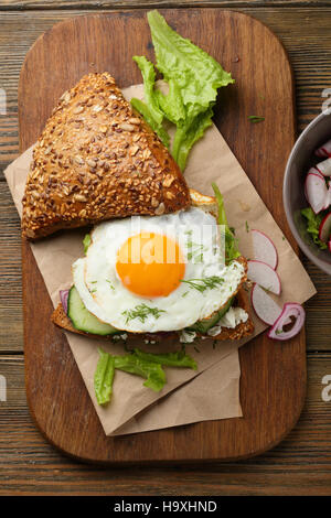 Breakfast sandwich with egg and lettuce on wood - Stock Photo