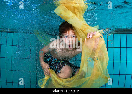 Surprised young boy playing under water in a swimming pool with some yellow cloth surrounded by bubbles - Stock Photo