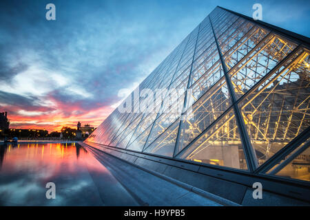 Sunset over the glass pyramid at the Louvre, Paris - Stock Photo