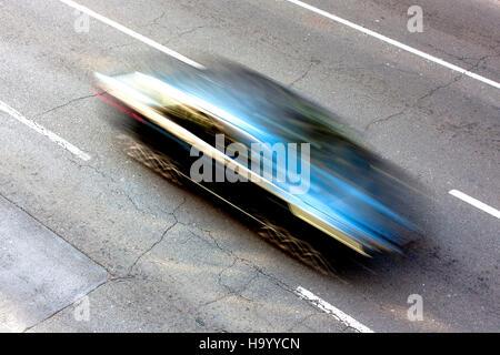 Blue car speeding on the street in motion blur - Stock Photo