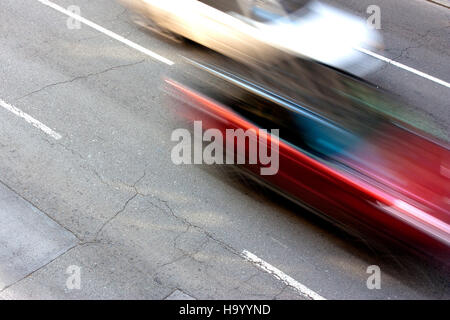 Two cars speeding on the street in motion blur - Stock Photo