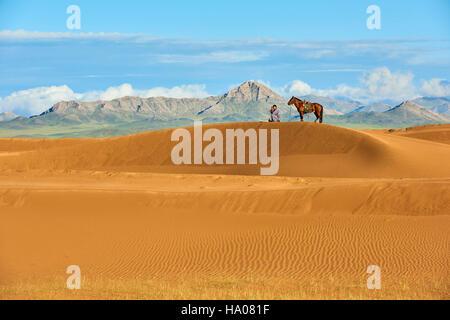Mongolia, Zavkhan province, Mongolian horserider in the sand dunes - Stock Photo