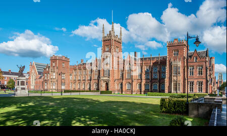 The Queen's University of Belfast with a grass lawn and a hedge in sunset light - Stock Photo