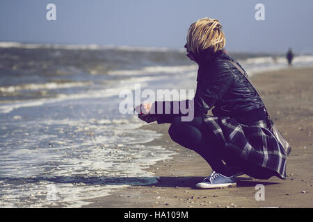 Young Caucasian blonde woman with black leather jacket and skirt crouched on sand in front of the ocean - Stock Photo