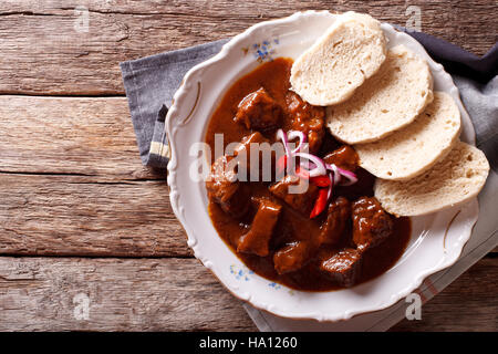 homemade hot Czech goulash with knodel in a plate close-up. horizontal view from above - Stock Photo