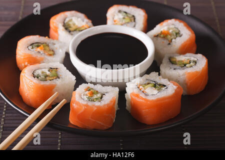 Sushi roll philadelphia and soy sauce , closeup on a plate. Horizontal - Stock Photo