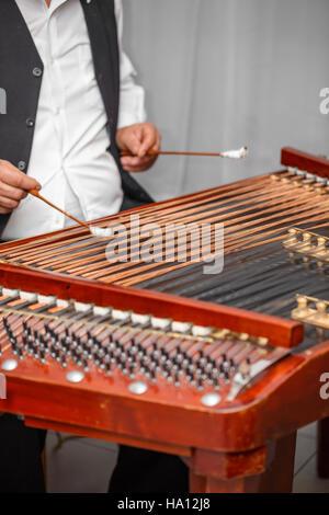 Man playing on wooden dulcimer musical instrument - Stock Photo