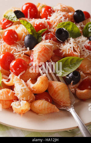 Italian pasta Conchiglie with tomatoes, olives and parmesan macro on a plate. vertical - Stock Photo