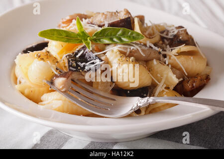 Pasta Conchiglie with porcini mushrooms and parmesan close-up on a plate. horizontal - Stock Photo