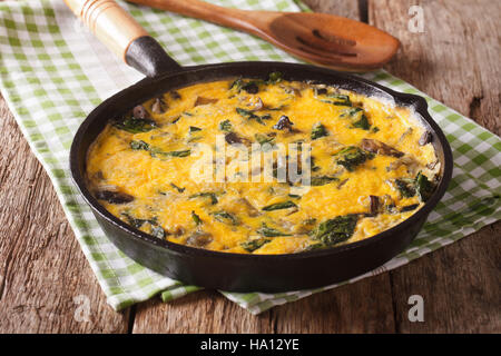 Hot scrambled eggs with spinach, cheddar cheese and mushrooms in a frying pan close-up on the table. horizontal - Stock Photo