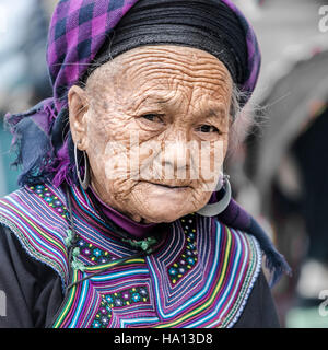 Black Hmong woman waiting for customers on the local market in Sapa, Vietnam, Asia - Stock Photo