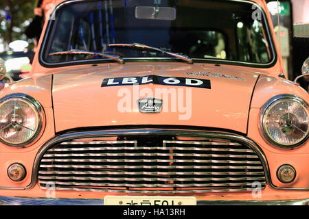 Tokyo, Japan-October 23, 2013: The lack of parking spaces on downtown Tokyo makes small cars as the classical-pink - Stock Photo