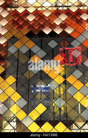 Gold-leaf laminated glasses on a diagonal cable-grid system on the facade of a modern building illuminated at night - Stock Photo