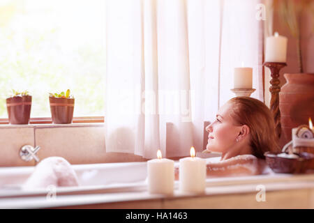 Beautiful girl spending time in the spa hotel, relaxing in the nice bath with foam, looking in the window, healthy - Stock Photo