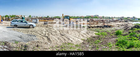 Landscape transform into urban area with machinery, people are working. Panorama view on construction site - Stock Photo