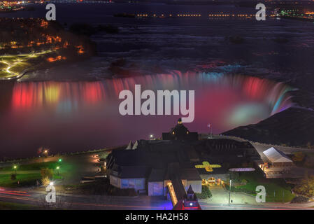 Aerial view Niagara Falls lit at night by colorful lights - Stock Photo