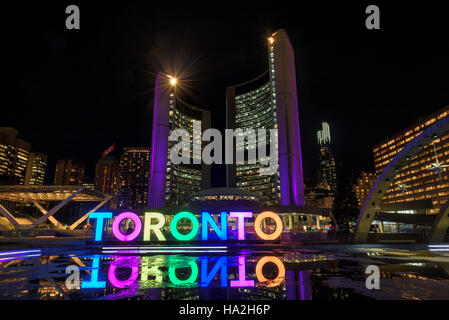 Toronto Sign with the illuminated City Hall at night, in Toronto, Canada - Stock Photo