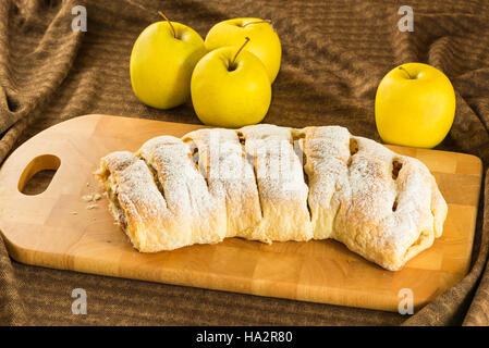 Homemade apple strudel (apples pie) with puff pastry, cinnamon and raisin on a chopping board - Stock Photo